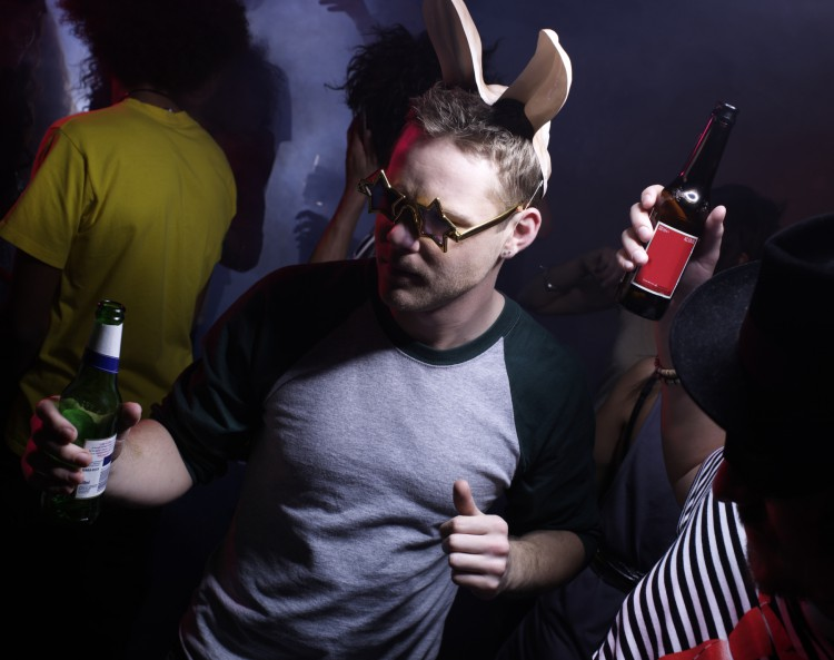 Young man wearing bunny ears, dancing in night club